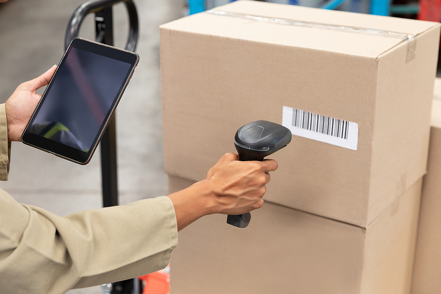 Close-up of female worker scanning package with barcode scanner