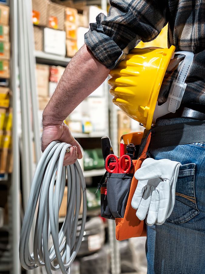 Electrician in the electrical component store holds the roll of electric cable in his hand, helmet with protective goggles. Construction industry, electrical system. View from behind.
