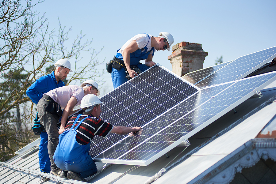 Workers installing commercial solar panel